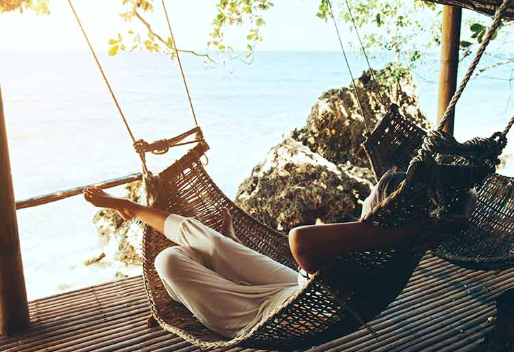 Woman relaxing in hammock by the sea