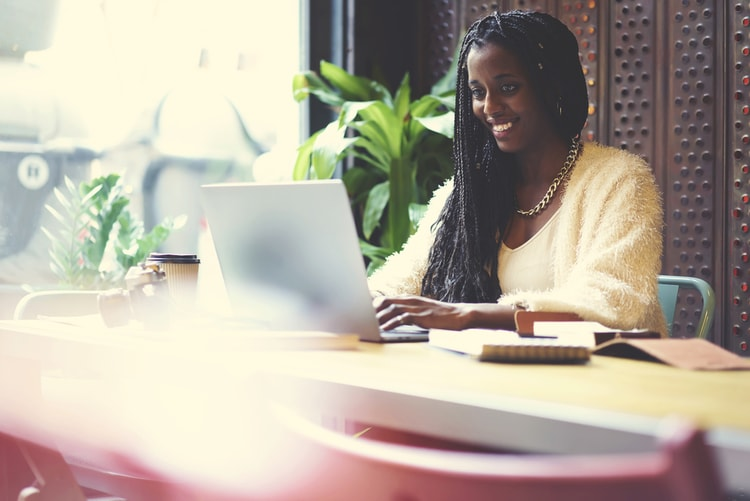 Young lady smiling while making a website